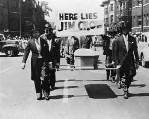 """1944 --- African-American men wearing tuxedos carry a coffin and a """"Here Lies Jim Crow"""" sign down the middle of a street as a demonstration against """"Jim Crow"""" segregation laws. 1944. --- Image by © CORBIS"""